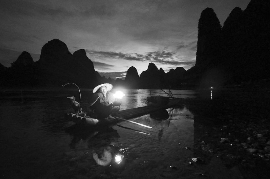 A picture of a cormorant fishermen with gas lamp on the li river