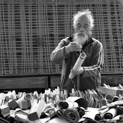 A Chinese man unwinding a scroll at the flea market