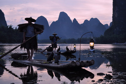Photo taken on a photography tour of xingping featuring two cormorant fishermen on a bamboo raftamboo raft at sunset